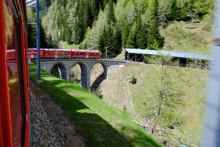 The red Bernina train travelling on the very famous viaduct symbol of the track