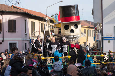 PARABIAGO (MI), ITALY - APRIL 9th 2019: some people dressed as skeletons throw confetti on the crowd during the parade of Carnival in Parabiago, near Milan, Italy.