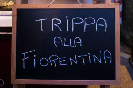 A sign with the Italian words Florentine tripe hung by a street food vendor