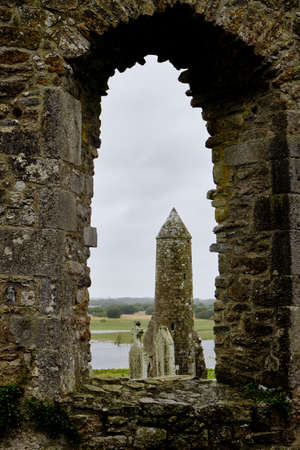 McCarthy's Tower seen through a cathedral window in the medieval monastery of Clonmacnoise, during a rainy summer day. It is situated in County Offaly, Ireland on the River Shannon south of Athlone.