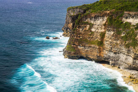 tropica: The cliffs and the ocean near the Uluwatu Temple on Bali, Indonesia.waves crashing against the cliff