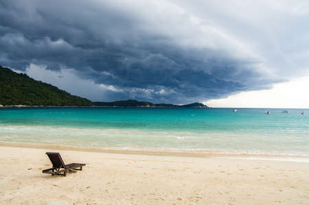 Lonely chaise longue on a deserted beach, against a background of approaching thunderstorm. Thunderclouds. Pulau Perhentian, Malaysia.