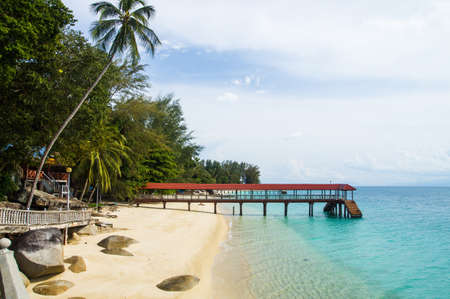 Relax on a deserted beach in an island of Tropical paradise. Pier on the beach at Pulau Perhentian, Malaysia.