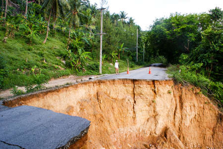 Washout: rain flood damaged badly washed out road in Thailand