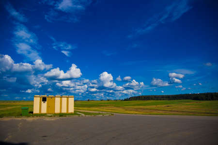 shower stall: A blue sky with clouds, asphalt, wood away and a roadside stall shower Stock Photo