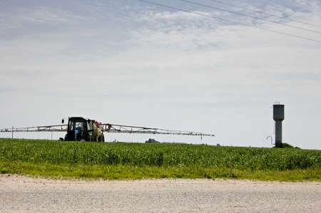 Rural landscape with the sky, a field, a water tower and a tractor spraying crops Stock Photo - 9240113