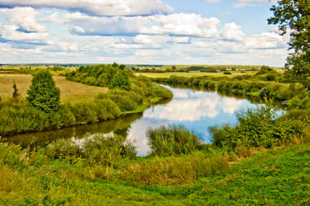 Summer landscape. On river turn, a grass, trees and the sky with clouds photo