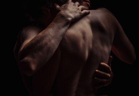 couple on a dark background hugs