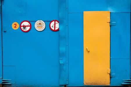 old metal doors: blue and yellow, with prohibition signs no smoking no fire