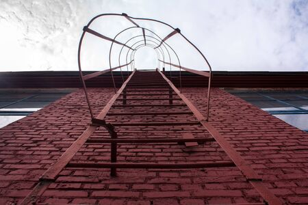 view from below of red street pompier ladder on the red wall without windows