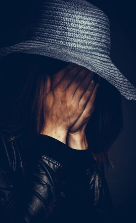 portrait of a sad girl in a hat, face covered with hands in dark colors