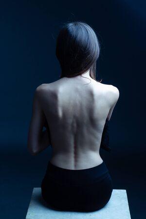 la jeune femme, le dos tourné, est assise sur une surface blanche, un fond sombre