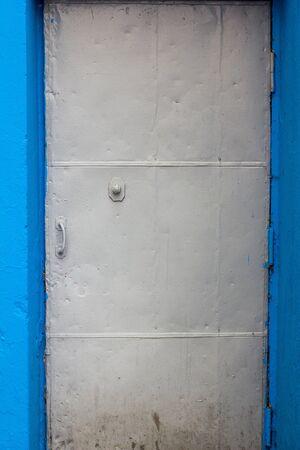metal textured gray door in a blue opening Stock Photo