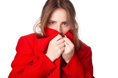 그 소녀는 그녀의 빨간 재킷 칼라 뒤에 그녀의 얼굴을 숨깁니다. 흰색 배경에 격리