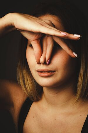 portrait of a girl on a black background, clip.pinch your nose with your fingers. The concept of bad smell, bad air ecology. Banque d'images - 133815752