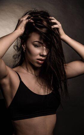 Studio portrait of a brunette girl in dark colors