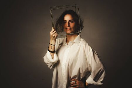 portrait of a girl in a white shirt with a metal cube-cage on his head. isolate on gray. The concept of estrangement, the man in a case Standard-Bild