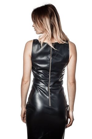 a girl in a black leather dress turned her back on a white background