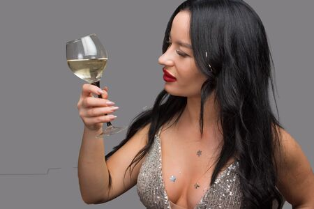 brunette on a grey studio background in a glass of white wine, with an open neckline in a shiny top with tinsel in her hair he looks at his glass on holiday or party