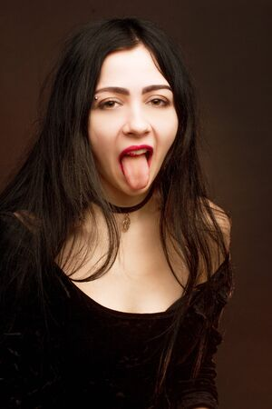 brunette on dark Studio background dressed in goth style, shows, sticks out his tongue