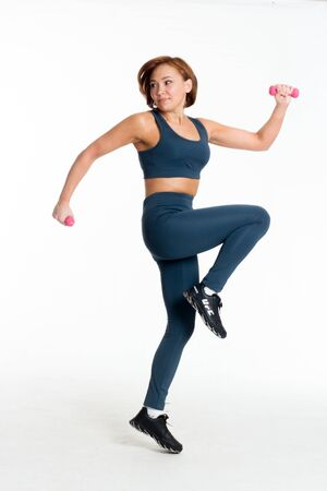 itness middle aged asian woman blue sweatpants and top jumps. Isolate white background with pink dumbbells