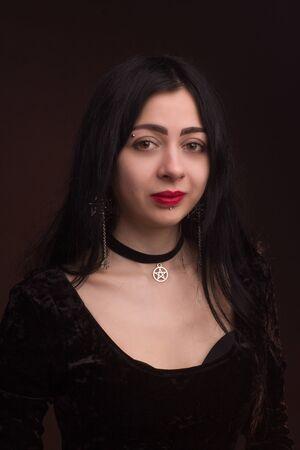 brunette on dark Studio background dressed in goth style