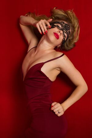 Dynamic studio shot of a young beautiful sexy woman in a red dress dancing on a red background in a black lace mask Stok Fotoğraf