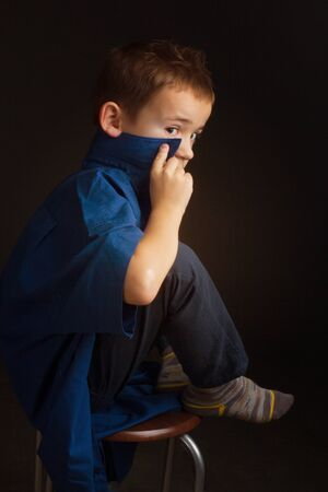 Studio portrait of a boy in a blue classic sweater, sitting on a chair, I put my foot on the chair, hiding his face behind the collar