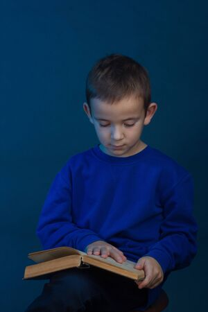 Studio portrait of a boy on a blue background in a classic t-shirt. With a book on her lap.