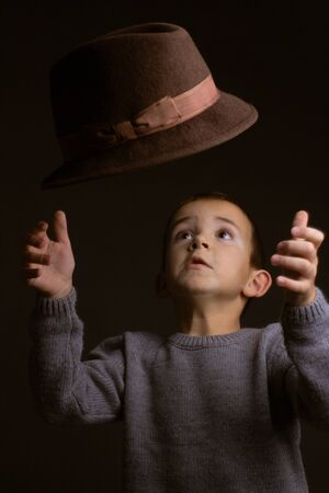 Studio portrait of a boy in a gray sweater, on a black background, tossing up a brown hat with his hands
