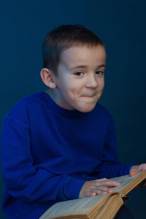 Studio portrait of a boy on a blue background in a classic t-shirt. With a book on her lap. smiles with compressed lips