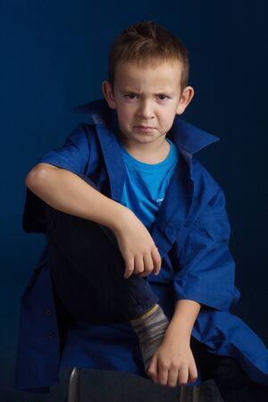 Studio portrait of a boy in a blue classic sweater, sitting on a chair, I put my foot on the chair