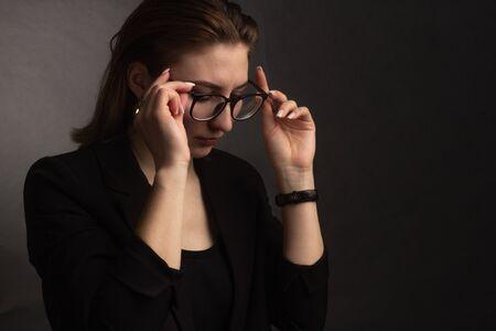 Retrato en la fotografía Estudio de una chica de cabello castaño, sobre un fondo negro en una chaqueta negra de negocios. Cabello corto. se golpea las gafas con las dos manos