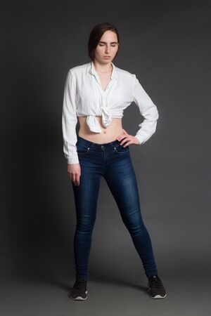 A life-size portrait of a girl in a white shirt, jeans and sneakers. On a dark gray Studio background. Looking down. left hand on hip, open the stomach 免版税图像