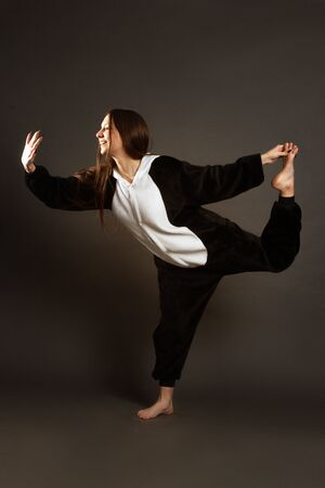 a portrait of growth of a brunette girl in the Studio on a plain black background in black and white pajamas with a hood, jumps, standing on one leg, the other behind, holding her hand
