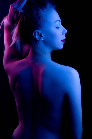 High Fashion model woman in colorful bright lights posing in studio, portrait of a beautiful girl. Artistic colorful design. Party concept, stands with his back Stockfoto