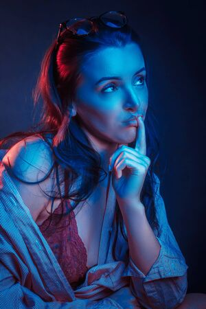 Fashionable Artistic Portrait Of A Beautiful Female Model In Bright Lights. resentful or brooding facial expression