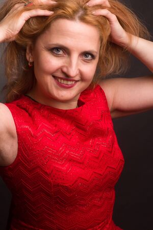 portrait of a large blonde model in a red dress on a dark background in the Studio Standard-Bild - 140464512