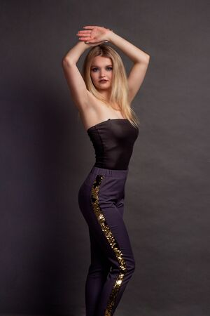 portrait of a blonde on a gray Studio background, in a black top off-the-shoulder and cleavage, and purple pants. standing sideways Standard-Bild - 140464669