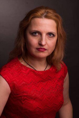 portrait of a large blonde model in a red dress on a dark background in the Studio Standard-Bild - 140464692
