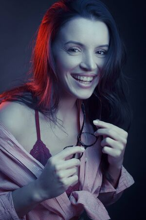Fashionable Artistic Portrait Of A Beautiful Female Model In Bright Lights. a pair of glasses in his mouth, winking. The concept of coquetry and play. laughing, happy Stock fotó