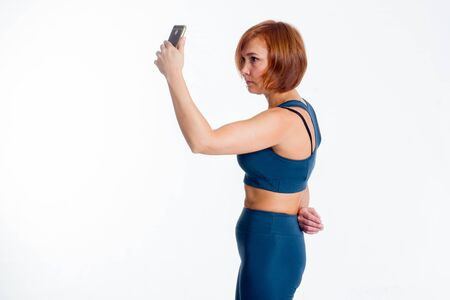 fitness middle-aged Asian woman in sportswear classic blue, makes a selfie Stockfoto