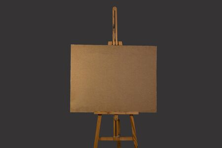 empty wooden tablet fixed horizontally on an easel, on a gray background isolated