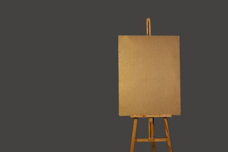 empty wooden tablet mounted vertically on an easel, on a gray background isolated Фото со стока