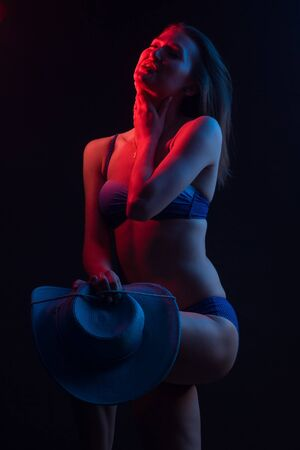 Fashionable Artistic Portrait Of A Beautiful Female Model In Bright backlit. in a wide-brimmed hat and swimsuit Banco de Imagens