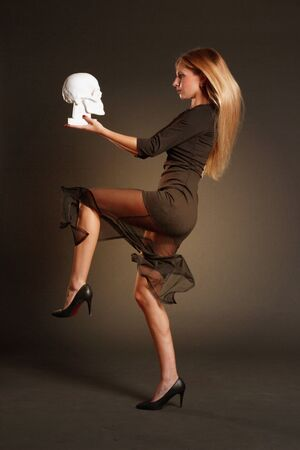 Portrait of a blonde with long hair, in a black dress on a dark background, holding a white plaster skull, stands sideways on one leg