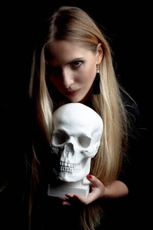 Portrait of a blonde with long hair, in a black dress on a dark background, holding a white plaster skull