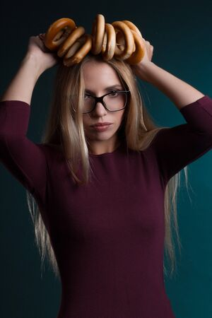 Portrait of a blonde with long hair, in a vinous suit, glasses, on a dark Turquoise Studio background. bunch of bagels on the head. Play The Fool