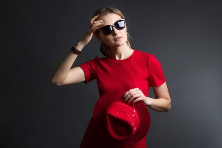 a blonde in a red dress, with a red hat and sunglasses poses on a dark Studio background