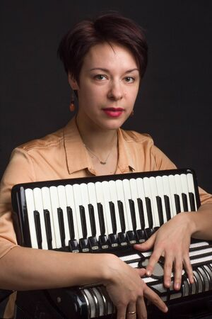 A brunette in a gold shirt, with a short haircut, on a dark background of the Studio. With accordion musician Stockfoto